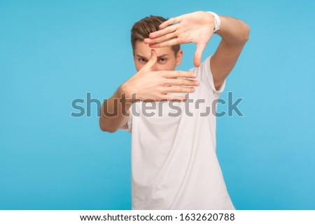 Portrait of curious man in white t-shirt gesturing picture frame with hands, looking through fingers and focusing on interesting moment, taking photo. indoor studio shot isolated on blue background
