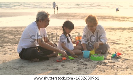 Grandfather and grandmother and niece playing sand on the beach. #1632630961