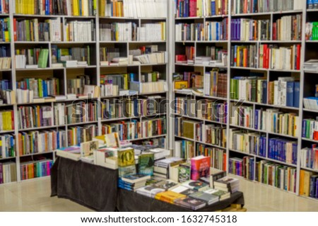 Large white bookshelves and small desk filled with books in a bookstore #1632745318