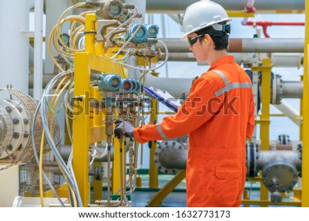 Technician operator checking and record reading value of pressure, temperature and flow transmitter in daily log book at offshore oil and gas central processing platform Royalty-Free Stock Photo #1632773173