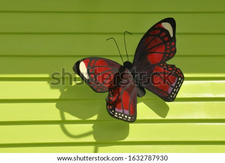 a wooden red and black butterfly against a lime green textured wall