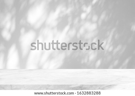 White Marble Table with Tree Shadow on Concrete Wall Texture Background, Suitable for Product Presentation Backdrop, Display, and Mock up. #1632883288