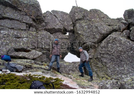 Southern Urals. Mature tourists make the ascent to the top along a large stone placer. #1632994852