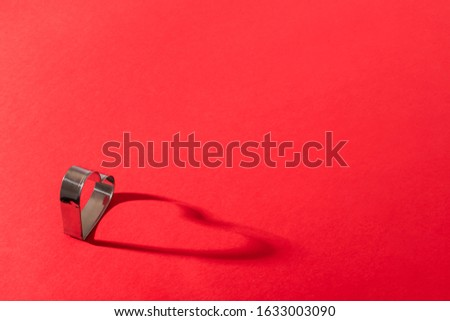 Metal shape in the shape of a heart on a red background and copy space. Valentine's day concept. Photo with a shadow #1633003090