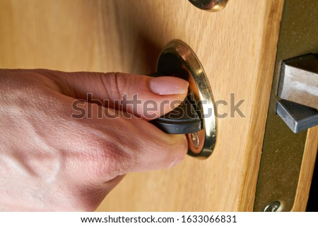 Locking up or unlocking door with key in hand Royalty-Free Stock Photo #1633066831