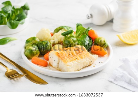 Fried cod fillet with steamed vegetables: baby carrots, Brussels sprouts, broccoli, cauliflower and corn salad on a white plate. Healthy food. Selective focus.