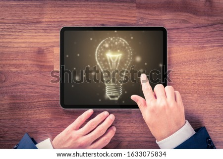 Creative company give you their creativity and ideas. Hands with digital tablet and graphics light bulb - symbols of idea, creative thinking, innovations and intelligence. #1633075834