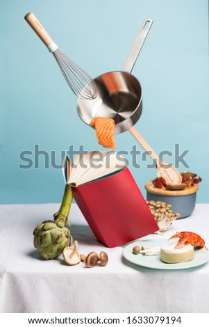 Concept of flying food preparation with seafood, artichoke, mushrooms and cheese using recipes book and stewpan with whisk. Art picture
