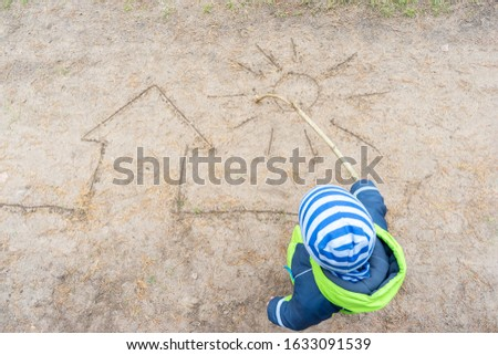 Little boy draws house and sun with stick on path in Park on sand. Concept of child development and happy childhood.
