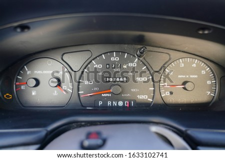 Fuel gauge, vehicle engine temperature, Miles Per Hour Speed indicator, and revolutions per minute indicator on a car dashboard in Fond du Lac, Wisconsin  Royalty-Free Stock Photo #1633102741