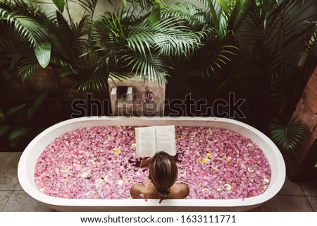 Woman reading book while relaxing in bath tub with flower petals. Organic spa relaxation in luxury Bali outdoor bath. #1633111771