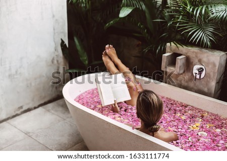 Woman reading book while relaxing in bath tub with flower petals. Organic spa relaxation in luxury Bali outdoor bath. #1633111774