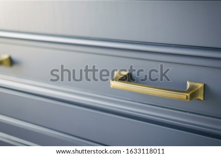 gold hardware on blue cabinets Royalty-Free Stock Photo #1633118011
