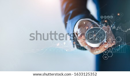 Businessman holding a navigation compass in hand and define marketing direction and analysis growth sale data with search customer global network, Abstract business.