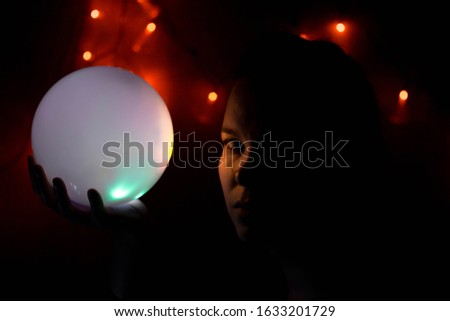 A girl in the dark with a glowing ball in her hand. Orange lights glow and light falls on the face of colored spots #1633201729