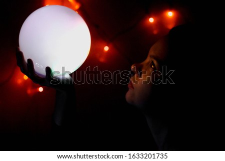 A girl in the dark with a glowing ball in her hand. Orange lights glow and light falls on the face of colored spots #1633201735