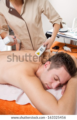 young man receiving laser epilation on beauty center #163325456