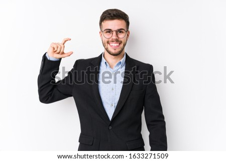 Young caucasian business man posing in a white background isolated Young caucasian business man holding something little with forefingers, smiling and confident. #1633271509