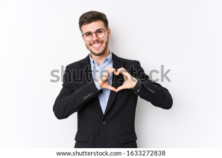 Young caucasian business man posing in a white background isolated Young caucasian business man smiling and showing a heart shape with hands. #1633272838