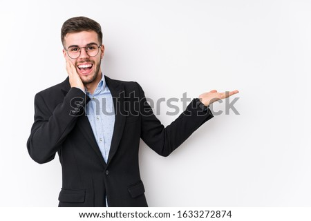 Young caucasian business man posing in a white background isolated Young caucasian business man holds copy space on a palm, keep hand over cheek. Amazed and delighted. #1633272874
