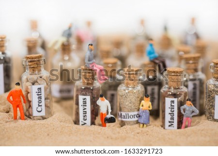 Glass test-tube with sand of different summer vacation destinations. Located in sand with small people figures. #1633291723