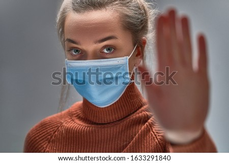Stop the virus and epidemic diseases. Healthy woman in blue medical protective mask showing gesture stop. Health protection and prevention during flu and infectious outbreak #1633291840
