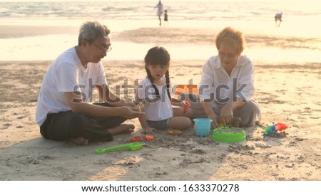 Grandfather and grandmother and niece playing sand on the beach. #1633370278