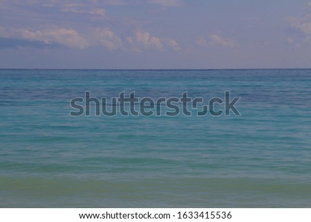 Picture of the Caribbean sea.The whole range of colors of sea water from turquoise at the shore to dark blue merging on the horizon with the sky and clouds.Mexico's Yucatan coast on a Sunny summer day