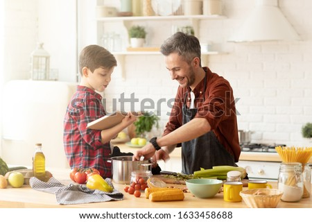 Son sitting on table reading funny book to dad cooking dinner at modern bright loft kitchen. Family spend time at home. Parent and child communication. Good relationships. Happy life. Fun recreation #1633458688