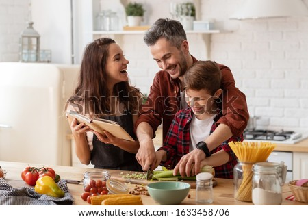 Happy family laughing loud. Mother, father and preschool son cooking on home kitchen. Mom holding cookbook. Dad helping child to chop celery for salad. Funny weekends. Communication and fun #1633458706