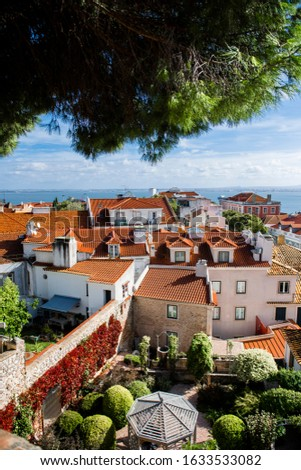 Lisbon view of the old town Alfama, Portugal, panorama. Lisboa colorful houses and red-tiled roofs. Hills with trees and historical buildings on a sunny day. Rooftops of the Portuguese city. #1633533082