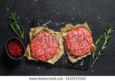 Home HandMade Raw Minced Beef steak burgers. Farm organic meat. Black background. Top view Royalty-Free Stock Photo #1633559362