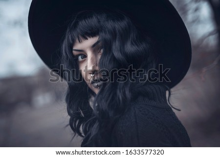 Dark gothic witch in black attire walking in the woods Royalty-Free Stock Photo #1633577320