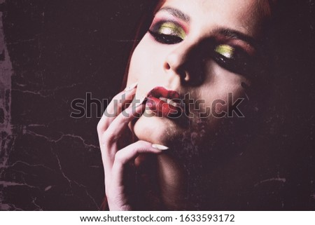Beautiful tender woman with sexy red lips and long fingers close to her open mouth. Fine Art photo. Toned Photo. Matte background. Vintage. Old photo. Copy space for your text.
