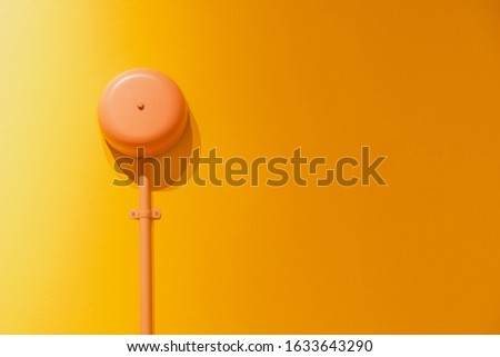 Pink signal bell buzzer on the orange wall background with copy space.Pastel tone with minimal style. #1633643290
