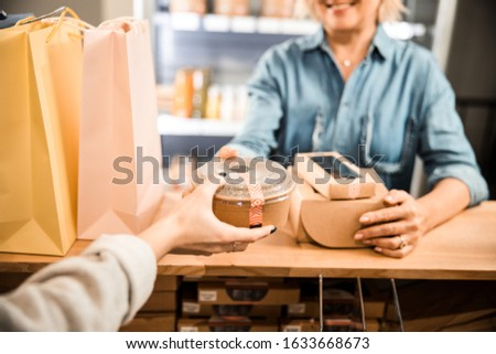 Cropped photo of cashier taking food box from mature lady in supermarket stock photo
