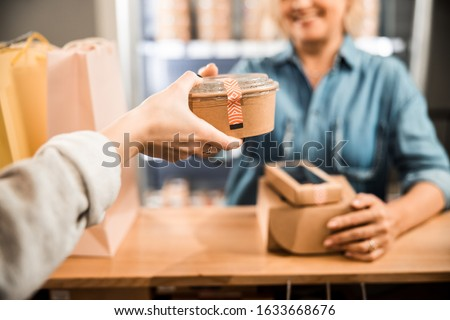 Cropped photo of cashier taking food box from woman in supermarket stock photo
