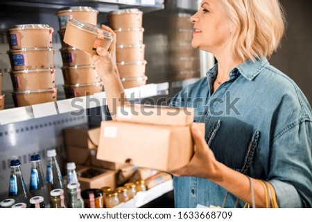 Cropped photo of happy attractive lady choosing products in the store stock photo
