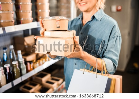 Cropped photo of smiling attractive woman choosing products in the store stock photo
