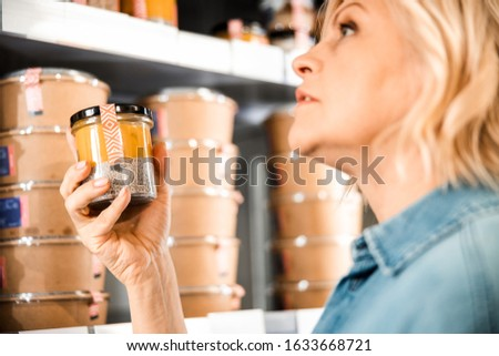 Cropped photo of mature female holding jar with dessert in store stock photo