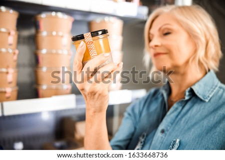 Cropped photo of happy adult lady holding jar with dessert in supermarket stock photo