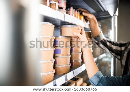 Cropped photo of man and woman taking food from a shelf in supermarket stock photo