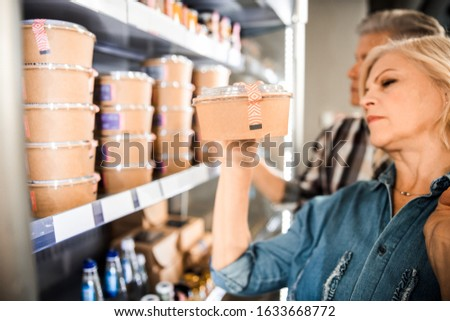Cropped photo of husband and wife taking food from a shelf in supermarket stock photo