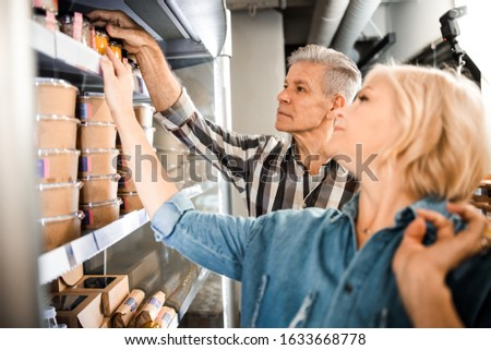 Cropped photo of adult man and woman choosing products in supermarket stock photo