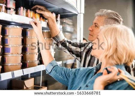 Cropped photo of mature couple choosing products in supermarket stock photo