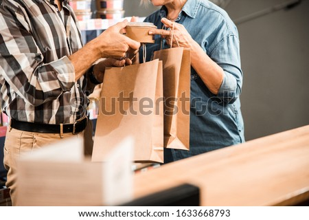 Cropped photo of adult man and woman standing with shopping bags stock photo