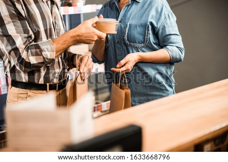 Cropped photo of mature man and woman standing with shopping bags stock photo