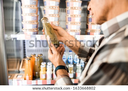 Cropped photo of adult man holding bottle with drink in shop stock photo