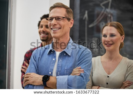 Best team. Joyful man crossing arms and smiling while standing in office with coworkers stock photo