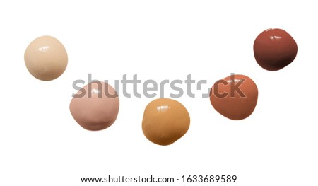 Makeup foundation texture. Liquid brown face cream drops of various shades isolated on white background. Beige color correcting concealer swatch